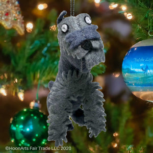 Cute little grey minature schnauzer felt Christmas ornament, hanging from a brightly decorated Christmas tree