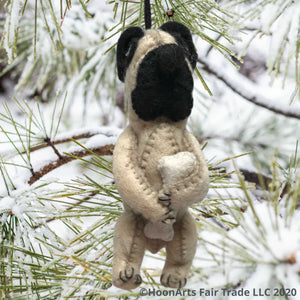 Adorable little pug (dog) felt Christmas ornament, handing from a snow covered pine tree