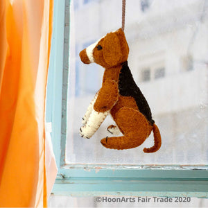 Handmade felt ornament from Kyrgyzstan-Beagle dog with black tan and white patches, seated on hind legs, hanging in front of a window with a blurred view of a multi-story building, framed by an aqua-colored wooden window frame and orange curtain to the left| HoonArts