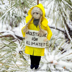 "Handmade Felt Ornament of Young Swedish Environmental Activist Greta Thunberg, dressed in bright yellow raincoat and knitted wool hat with long blond brains, carrying a white sign that says ""SKOLSTREJK FOR KLIMATET"" [school strike for climate]. She is hanging from a snow covered pine tree with long pine needles."
