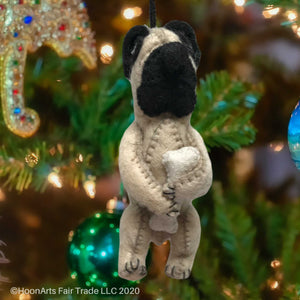 Handmade Dog Christmas Ornament-Light Tan Pug with black ears and snout, holding a bone and hanging from a brightly decorated Christmas tree