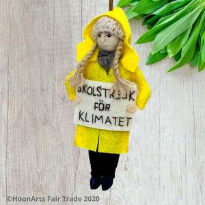 "Handmade Felt Ornament of Young Swedish Environmental Activist Greta Thunberg, dressed in bright yellow raincoat and knitted wool hat with long blond brains, carrying a white sign that says ""SKOLSTREJK FOR KLIMATET"" [school strike for climate]. She is hanging in front of a very light colored wooden wall with a collection of small green leaves  in the upper right corner."