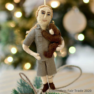 Handmade Felt Ornament of Jane Goodall, Dressed in Khaki Camp Shirt and Shorts, with her hair in a ponytail, and holding a dark brown chimpanzee in her left arm like a young child, against a blurred image of a brightly lit Christmas tree