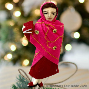Handmade felted Christmas ornament of Malala, young Pakistani activist for girls' education, dressed in a deep red dress with a bright pink sari with scattered gold beaded sunbursts wrapped around her head and body, holding a book in her right hand. She's hanging in front of a blurred image of a Christmas tree with  bright white  lights.