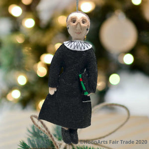Handmade Felt Ornament-RBG Wearing Black Judicial Robes with Big White Color and Large Eyeglasses, Carrying a Law Book, Hanging against a blurred image of a brightly lit Christmas tree