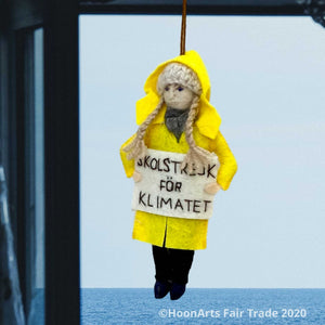 "Handmade Felt Ornament of Young Swedish Environmental Activist Greta Thunberg, dressed in bright yellow raincoat and knitted wool hat with long blond brains, carrying a white sign that says ""SKOLSTREJK FOR KLIMATET"" [school strike for climate]. She is hanging from a blue window frame looking out over a calm blue ocean."