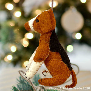 Handmade felt ornament from Kyrgyzstan-Beagle dog with black tan and white patches, seated on hind legs, hanging in front of a blurred image of  a Christmas tree with bright white lights | HoonArts