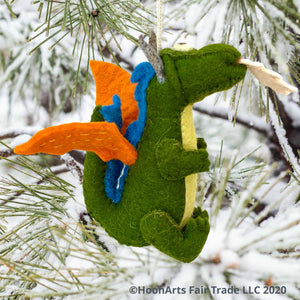 "Side view of Handmade Kyrgyz green felt dragon ornament with orange wings, blue accents along the middle of the back,  big black eyes on white and white ""flames"" shooting from mouth, hanging from a snow covered pine tree with long pine needles 