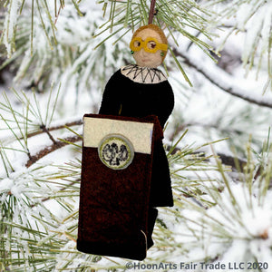Handmade Ruth Bader Ginsburg with Podium, dressed in black judicial robes, hanging from a snow-covered pine tree