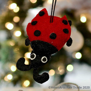 Bright red and black felt ladybug Christmas ornament, hanging in front of a blurred background of Christmas twinkle lights