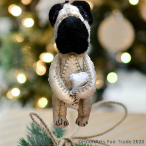 Cute little  handmade tan pug (dog) ornament, clutching a bone, hanging against a brightly lit background with Christmas twinkle lights