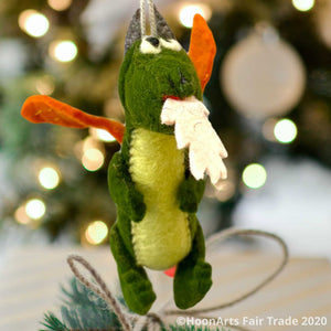 "Handmade Kyrgyz green felt dragon ornament with orange wings, big black eyes on white and white ""flames"" shooting from mouth, hanging in front of a blurred image of a Christmas tree with bright white lights 