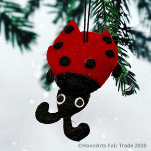 Bright red and black felt ladybug ornament, hanging from the tips of a pine Christmas tree