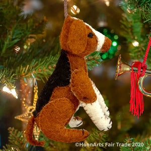 Handmade felt ornament from Kyrgyzstan-Beagle dog with black tan and white patches, seated on hind legs, hanging from a Christmas tree with brightly colored ornaments | HoonArts