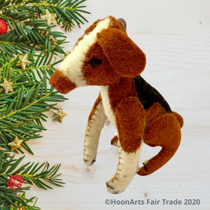 Handmade felt ornament from Kyrgyzstan-Beagle dog with black tan and white patches, seated on hind legs, seated on a whitewashed wooden table with small pine branch tips decorated with small gold starts along the left side of the image| HoonArts