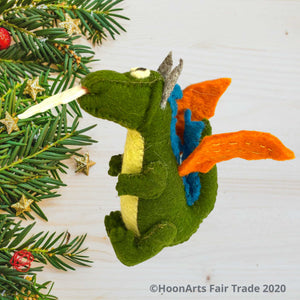 "Side view of Handmade Kyrgyz green felt dragon ornament with orange wings, blue accents along the middle of the back, big black eyes on white and white ""flames"" shooting from mouth, sitting on a white washed wooden table with pine branch tips decorated with tiny gold stars along the left side of the image
