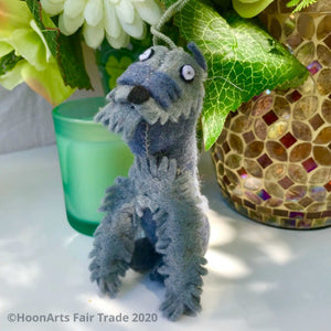 Little miniature schnauzer felt ornament, seated on a table in front of a votice candle and mosaic vase