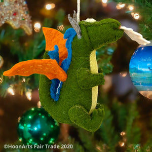 "Handmade green felt dragon ornament with orange wings and blue accent along the back, with big eye and white ""flames"" shooting from mouth, hanging on a Christmas tree with brightly colored bulbs 