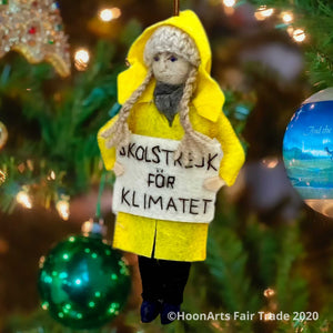 "Handmade felt ornament of Greta Thunberg, young environmental activist from Sweden, dressed in Yellow Raincoat, with long blond braids and a knitted wool hat, hanging from a brightly lit Christmas tree. She is carrying a white sign with the words ""SKOLSTREJK FOR KLIMATET"" [school strike for climate]"
