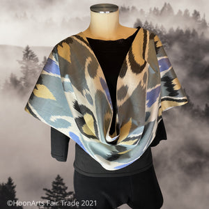Elegant handwoven silk ikat infinity shawl, in traditional Uzbek pattern, with grey, white, black, blue & beige, draped on mannequin  | HoonArts