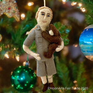Handmade Felt Ornament of Jane Goodall, Dressed in Khaki Camp Shirt and Shorts, with her hair in a ponytail, and holding a dark brown chimpanzee in her left arm like a young child, hanging from a Christmas tree with colorful balls and white lights.