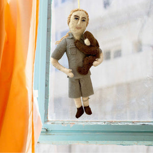 Handmade Felt Ornament of Jane Goodall, Dressed in Khaki Camp Shirt and Shorts, with her hair in a ponytail, and holding a dark brown chimpanzee in her left arm like a young child, hanging in front of a window overlooking a tall building, with an aqua-colored wooden window frame and a bright apricot-colored curtain to the left.
