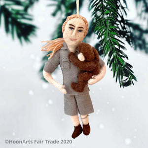 Handmade Felt Ornament of Jane Goodall, Dressed in Khaki Camp Shirt and Shorts, with her yarn hair in a ponytail, and holding a dark brown chimpanzee in her left arm like a young child, hanging in front of the tips of a pine tree against a white background.