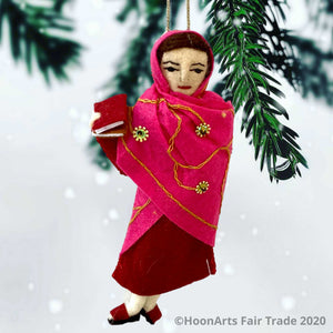 Handmade felted Christmas ornament of Malala, young Pakistani activist for girls' education, dressed in a deep red dress with a bright pink sari with scattered gold beaded sunbursts wrapped around her head and body, holding a book in her right hand. She's hanging  in front of a white background with pine branch tips hanging down at the top of the image.