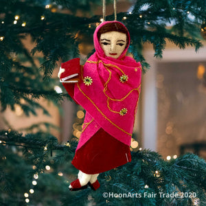 Handmade felted Christmas ornament of Malala, young Pakistani activist for girls' education, dressed in a deep red dress with a bright pink sari with scattered gold beaded sunbursts wrapped around her head and body, holding a book in her right hand. She's hanging from a pine tree with small white twinkling lights.