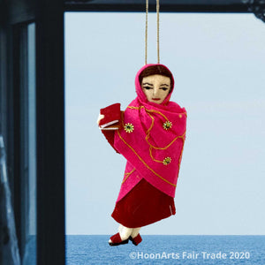 Handmade felted Christmas ornament of Malala, young Pakistani activist for girls' education, dressed in a deep red dress with a bright pink sari with scattered gold beaded sunbursts wrapped around her head and body, holding a book in her right hand. She's hanging in front of a window overlooking a calm blue ocean, with blue curtains on the left