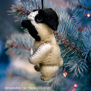 Felt Pug Christmas Ornament, holding a bone, hanging from a Christmas tree
