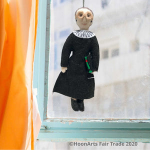 Ruth Bader Ginsburg Handmade Felt Figure, Dressed in Black Judicial Robes and White Color, Wearing Her Signature Big Glasses, Carrying Her Law Book. She's hanging in front of a window with an aqua-colored wooden frame and an apricot colored curtain to the left