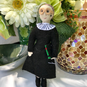 RBG Felt Ornament from Kyrgyzstan, Dressed in Black Judicial Robes and White Collar, Big Glasses, Carrying a Law Book, Against a Background of Flowers, a Silver Candy Dish and a Golden Mosaic Vase