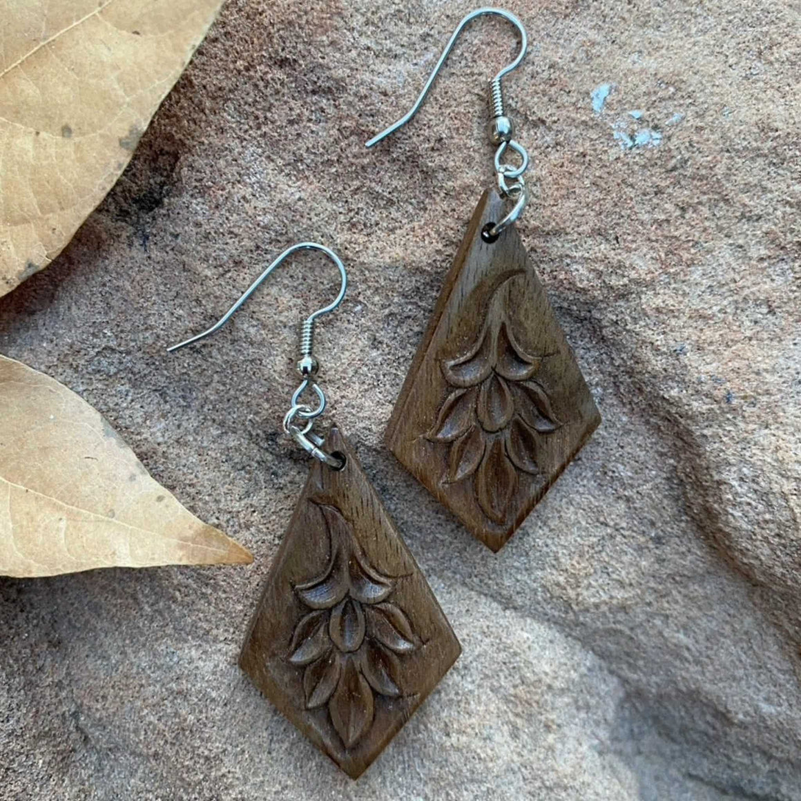 Handcarved walnut earrings in upside-down kite shape with floral patterns and surgical steel ear wires