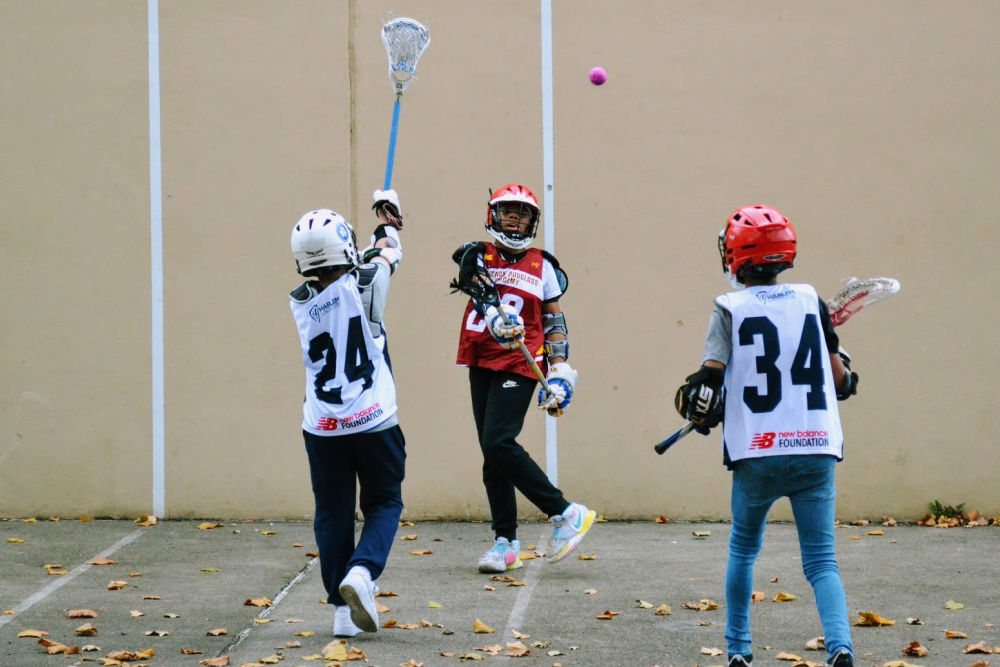 Girls from Harlem Lacrosse playing on hard concrete surface