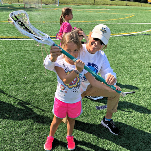 Coach and Mom Laura Gump teaching young girl how to play lacrosse using a Swax Lax ball
