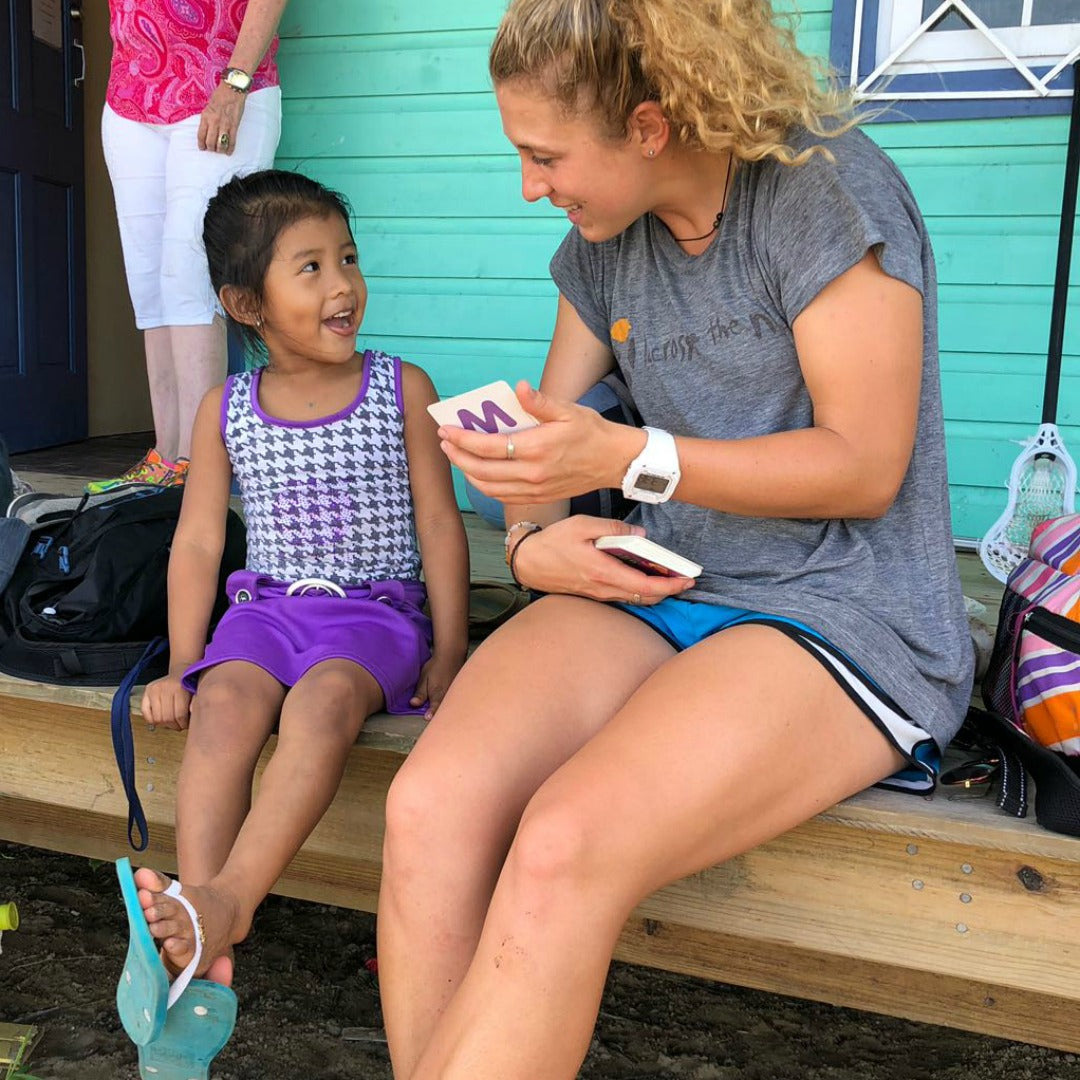 Coach Brooke Wilson talking to young girl - Lacrosse the Nations