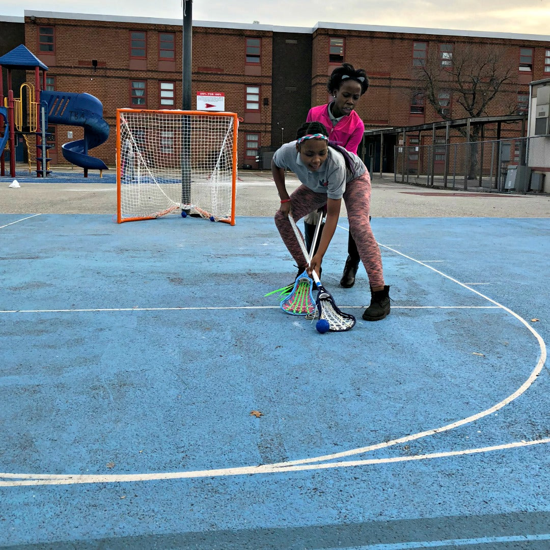 Harlem Lacrosse playing outdoors using a Swax Lax soft lacrosse training ball