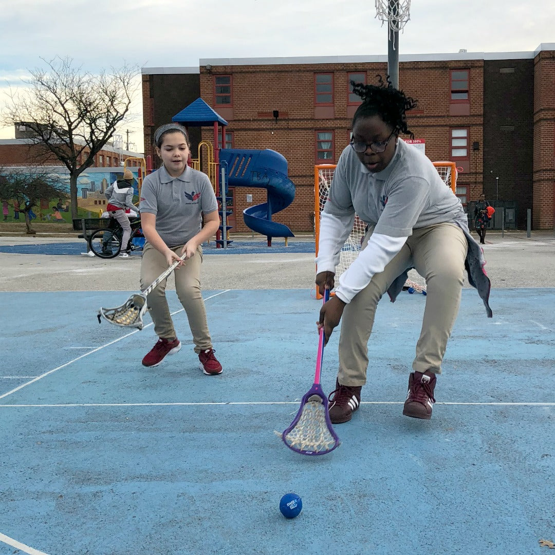 Girls from Harlem Lacrosse going to scoop a Swax Lax lacrosse training ball