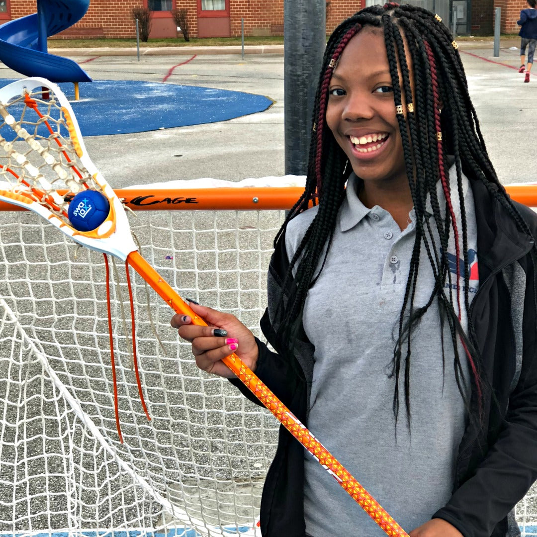 Harlem Lacrosse girl holding a blue Swax Lax ball in her lacrosse stick