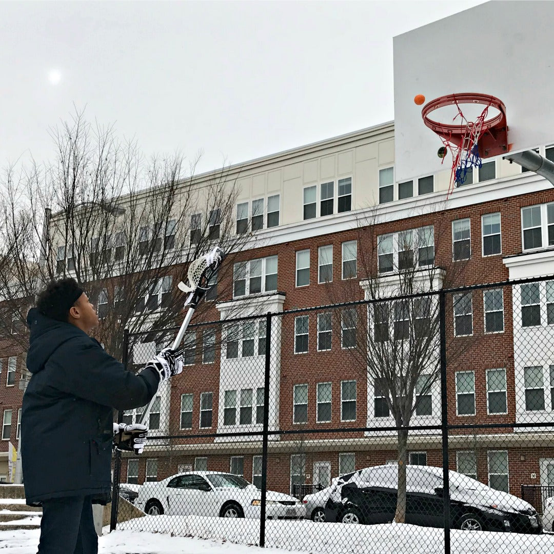 Harlem Lacrosse boy having fun shooting a Swax Lax soft lacrosse training ball into a basketball net