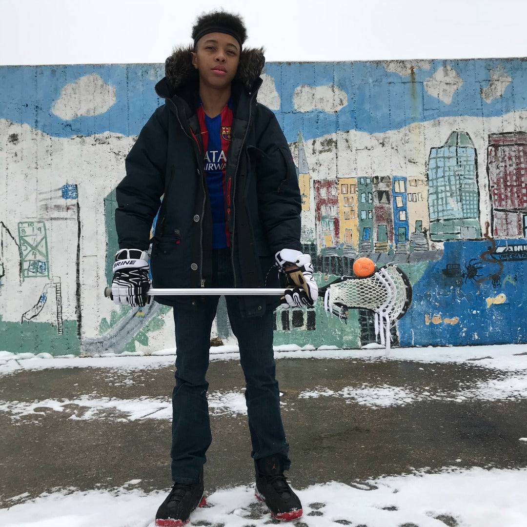 Harlem Lacrosse boy balancing a Swax Lax ball on his lacrosse stick
