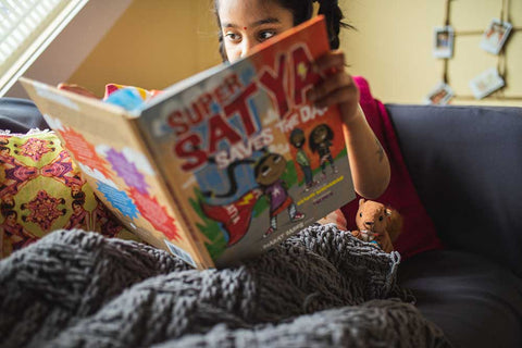 Girl reading Super Satya Saves the Day