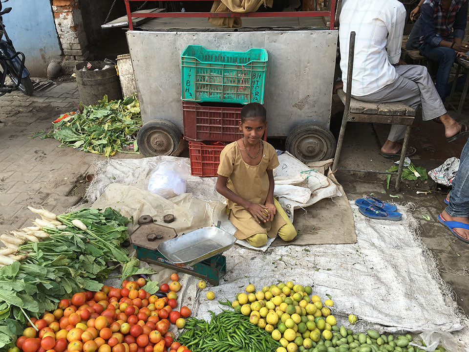 A young India girl selling citrus fruits and vegetable with her brother - Main Street Oriental Rugs