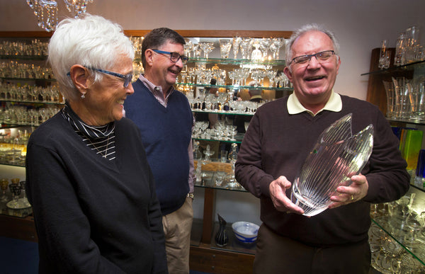 While holding a vase, Kusak Cut Glass Works CEO Chuck Kusak shares a laugh with longtime customers Marna and Ed Pettigrew, of Mercer Island, in the showroom of his Seattle store. The building has been sold, and the 104-year-old glass-artisan business will close. (Ellen M. Banner/The Seattle Times)
