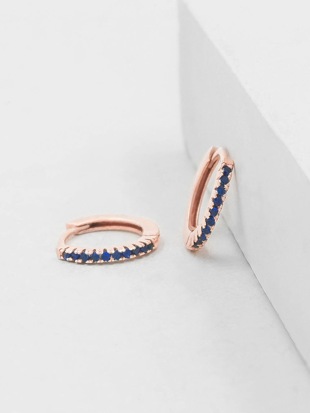 Rose gold plated Super Dainty Hoop Huggie Earrings with Tiny Blue Sapphire Round Cubic Zirconia by The Faint Hearted Jewelry