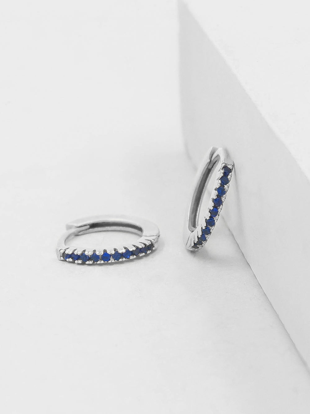 Silver Super Dainty Hoop Huggie Earrings with Blue Sapphire Round Cubic Zirconia by The Faint Hearted Jewelry