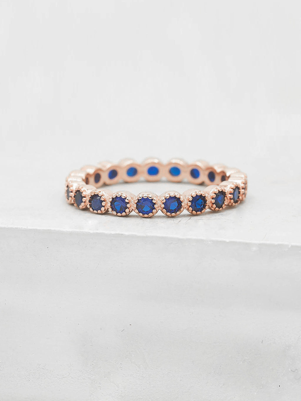 Rose Gold Plated Bezel Set Round Blue CZ Eternity Ring by The Faint Hearted Jewelry