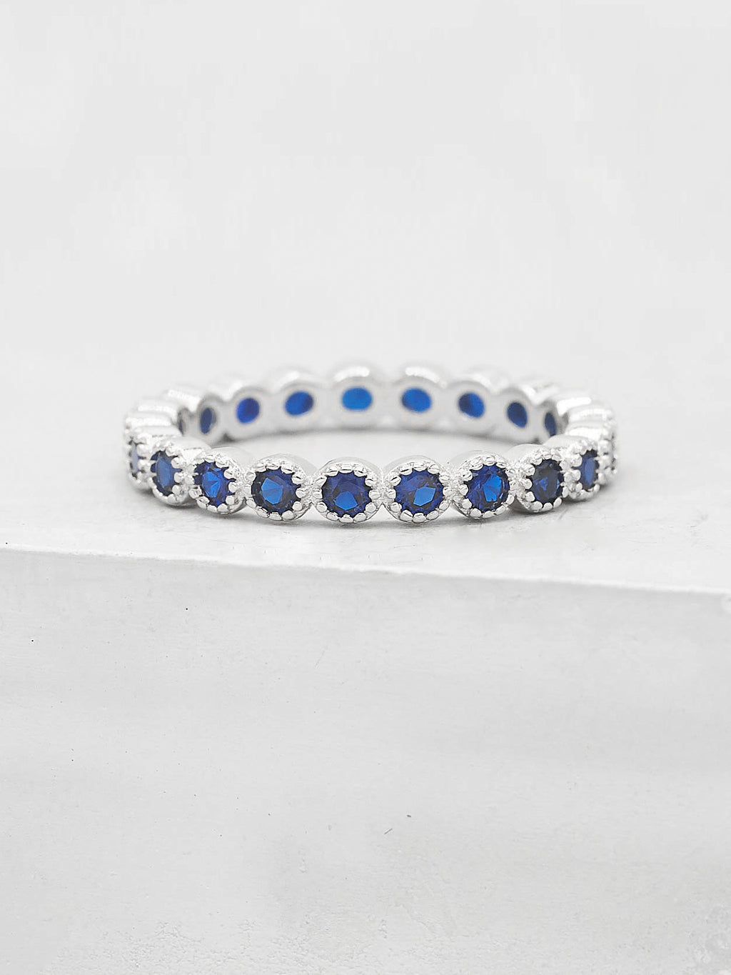 Rhodium Plated Eternity Design Ring with Blue Round CZ by The Faint Hearted Jewelry