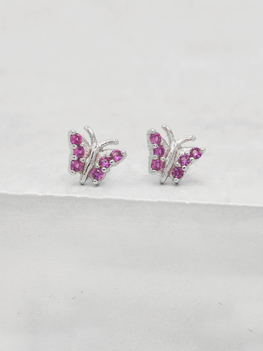 Rhodium Plated  Tiny butterfly with Pink CZ cubic Zirconia Dainty Stud Earrings by The Faint Hearted jewelry